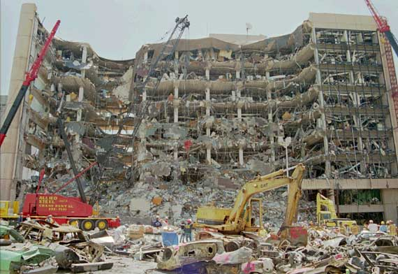 Heavy equipment is used to remove debris from the front of the Alfred P. Murrah Federal Building in downtown Oklahoma City Friday, April 21, 1995, site of Wednesday's car bombing that left at least 50 people dead and scores injured or missing.(AP Photo/David Glass)